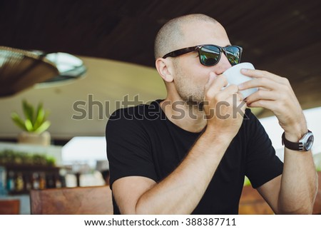 Coffee time. Handsome young man enjoying coffee in cafe while sitting at the table with digital tablet laying near him - stock photo