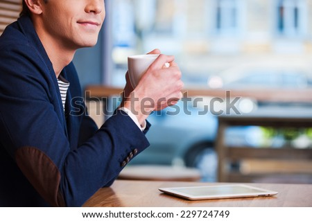 Coffee time. Side view cropped image of handsome young man enjoying coffee in cafe while sitting at the table with digital tablet laying near him  - stock photo