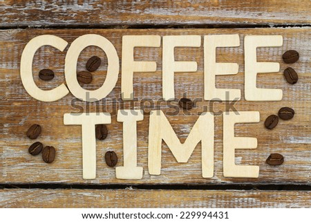 Coffee time written with wooden letters on rustic wooden surface