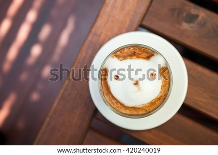 Coffee topping bear made with milk foam. Cup of hot coffee place on the wood table. - stock photo