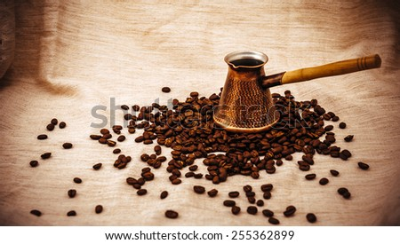 Coffee turk and cup of coffee on burlap background. coffee beans isolated on white background. roasted coffee beans - stock photo