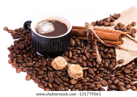 Coffee with coffee beans, cinnamon sticks, white and brown sugar isolated on white