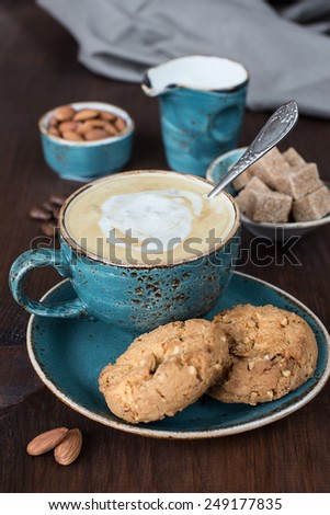 Coffee with cream  in blue vintage cup and cookies on a old dark wooden boards - stock photo