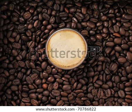 Coffee with cup and cream in coffee beans - stock photo