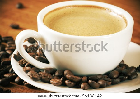Coffee with froth in white cup and coffee beans on wooden table. - stock photo