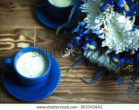 coffee with milk and flowers on wooden background still life - stock photo