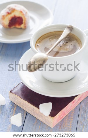 Coffee with milk and sweet dessert. Bitten donut with icing sugar - stock photo