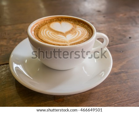 coffee with milk in a cup on wooden table