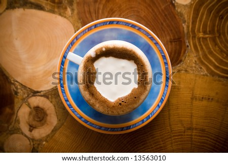Coffee with milk on wooden table from top - stock photo
