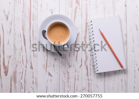 Coffee with notepad and pencil on white wood table. - stock photo