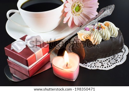 Coffee with red gift box, burning candle and chocolate cake on black - stock photo