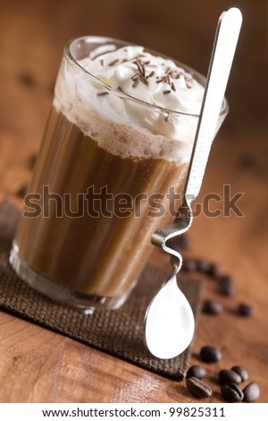 Coffee with whipped cream and pieces of chocolate in the glass - stock photo