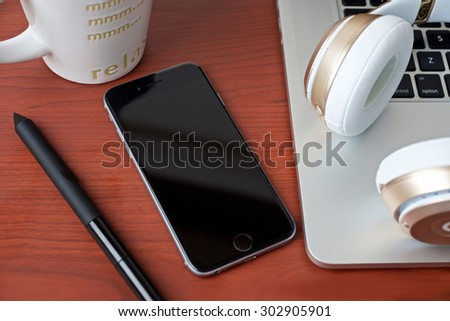 Coffee work table with mobile phone and laptop and a headphone on a wooden pattern table surface top view - stock photo