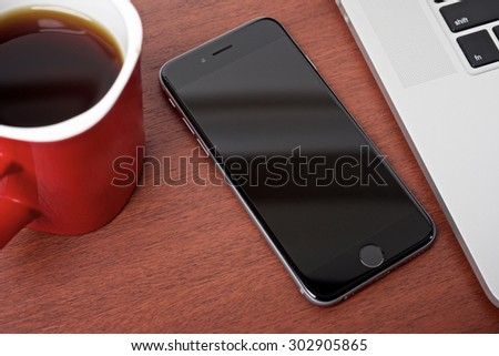 Coffee work table with mobile phone and laptop on a wooden pattern table surface top view - stock photo