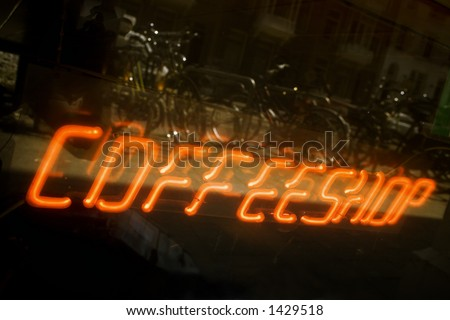 coffeeshop in amsterdam with bicycles reflected in the window - stock photo
