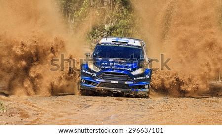 COFFS HARBOUR, AUSTRALIA - SEPTEMBER 14, 2014: Finnish crew M. HIRVONEN J. LEHTINEN M-Sport World Rally in a Ford Fiesta RS at WRC 2014 race with water splash - stock photo