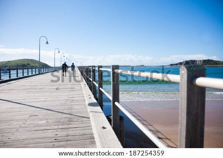 COFFS HARBOUR, NEW SOUTH WALES, AUSTRALIA - MARCH 22; distant figures of two people walking out on the pier on March 22, 2014 in Coffs harbour, Australia.