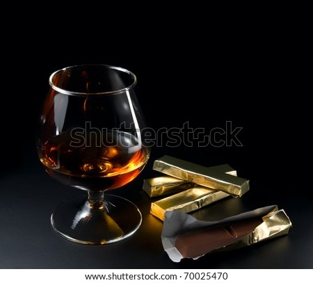 Cognac and chocolate on a black background. - stock photo