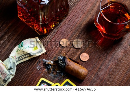 cognac and cigar card money on a wooden background. concept of the game cards. Wild West. Disorder on a table in the saloon in America. - stock photo