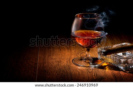 Cognac and cigar on ashtray on a wooden table - stock photo