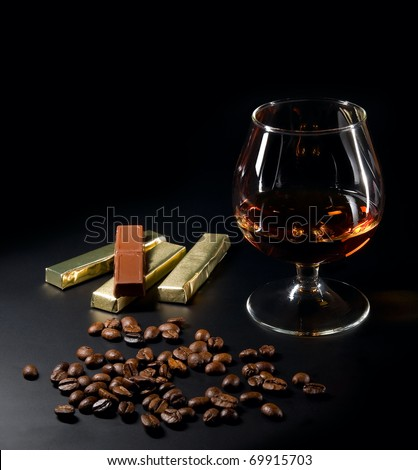 Cognac and coffee beans and chocolate on a black background. - stock photo