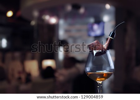 cognac and pipe on a dark background. - stock photo
