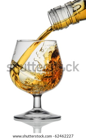 cognac being poured into a glass - stock photo