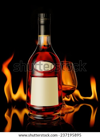 Cognac bottle and a glass in front of fireplace - stock photo