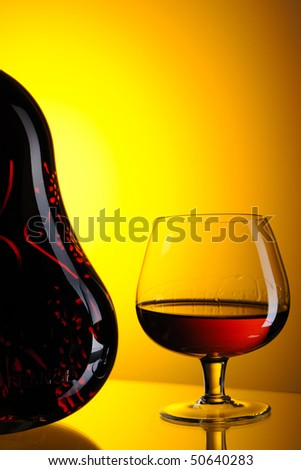 Cognac bottle and glass still life - stock photo