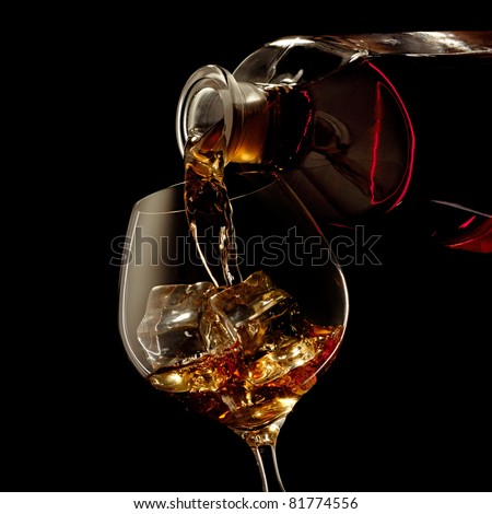 Cognac glass and bottle on a black - stock photo