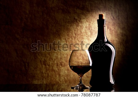 Cognac Glass and Bottle on a old stone background - stock photo