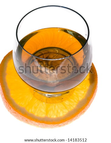 Cognac glass and slice of orange on white