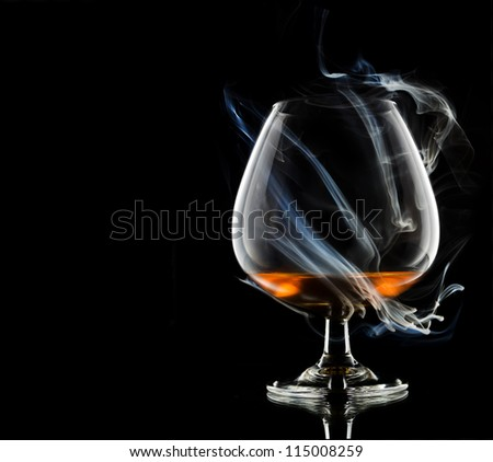 Cognac glass shrouded in a smoke - stock photo