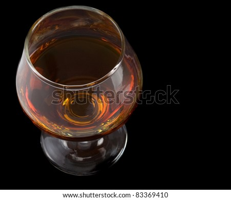 cognac glass with brandy isolated on black - stock photo