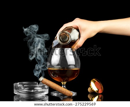 Cognac in bottle, glass and cigar on black background - stock photo
