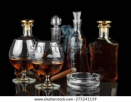 Cognac in bottles and glasses and cigar - stock photo