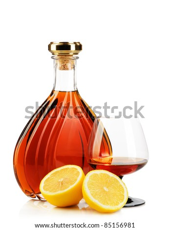 Cognac in bottles with glass and lemons on white background - stock photo