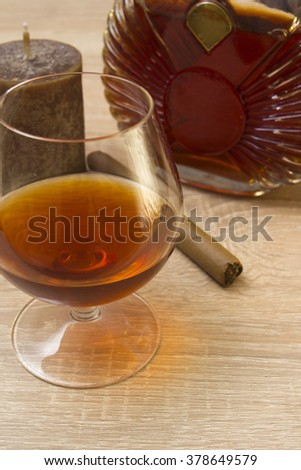 Cognac in glass and cigar on a wooden surface - stock photo