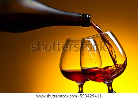 Cognac poured into a glass on a yellow background