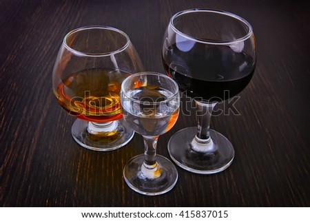 cognac vodka wine in three glasses on a table - stock photo