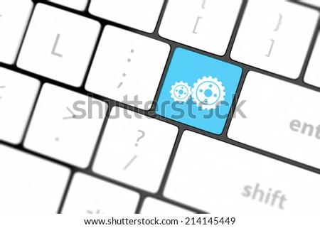 cogwheel gear mechanism on button on white computer keyboard. - stock photo