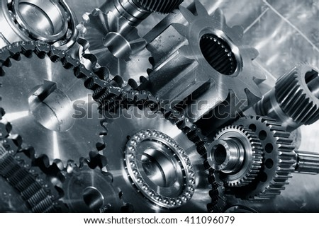 cogwheels and gears in titanium, aerospace engineering parts in a metal toning concept - stock photo