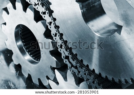 cogwheels and gears powered by large chains, blue toning concept - stock photo