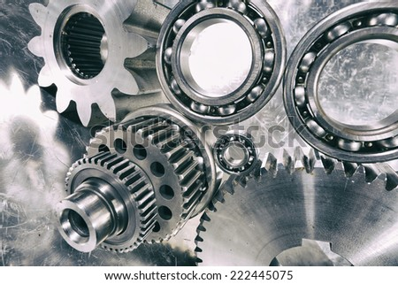 cogwheels, gears and ball-bearings, titanium and steel engineering parts - stock photo