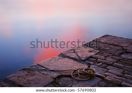 Coil of rope on a jetty, next to calm sea in Swanage, Dorset - stock photo