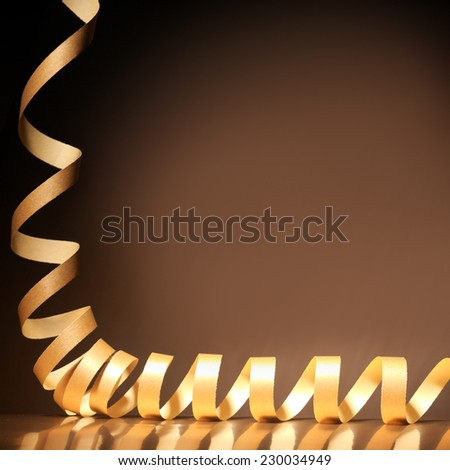 Coiled festive gold ribbon Christmas or holiday celebration border on a reflective brown background with copyspace for your greeting or congratulations - stock photo
