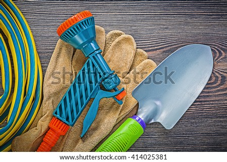 Coiled garden rubber hose leather safety gloves hand shovel on wood board gardening concept.