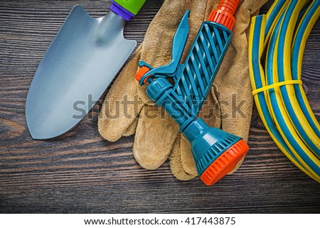 Coiled garden rubber hose protective gloves hand spade on wood board agriculture concept.