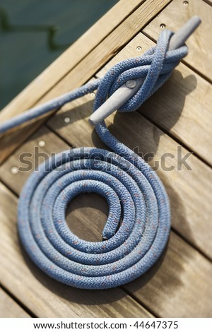 Coiled rope tied to docking cleat. Vertically framed shot. - stock photo