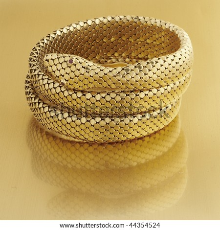 Coiled snake bracelet in gold mesh with ruby eyes on gold surface